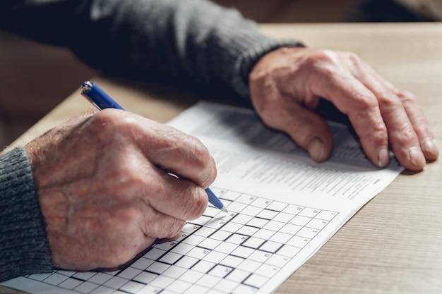 Elderly man solves sudoku or a crossword puzzle