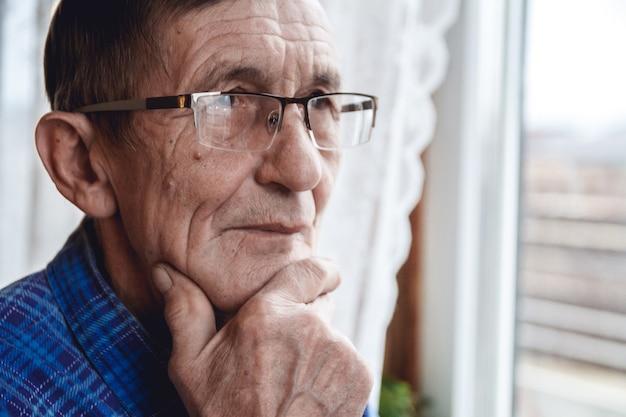 Пожилой мужчина, стоящий у окна