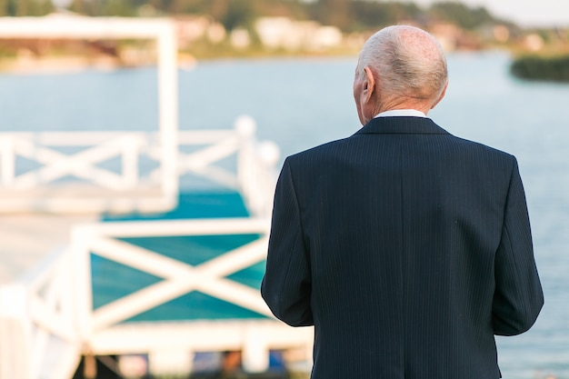 An elderly man standing back to camera near pier on the lake. wearing business suit.