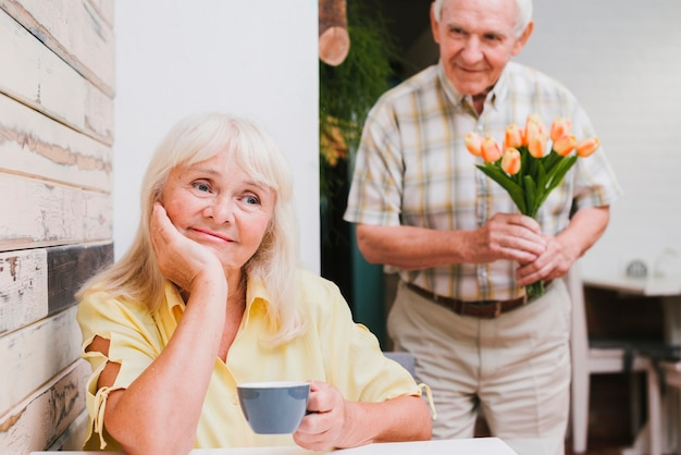 Elderly man standing behind beloved with flowers