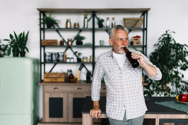 An elderly man standing in front of kitchen counter drinking beer