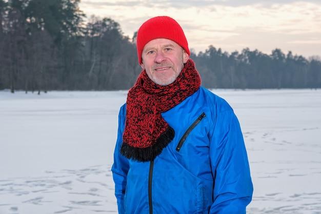 運動後に休んでいる冬の森に立っている老人