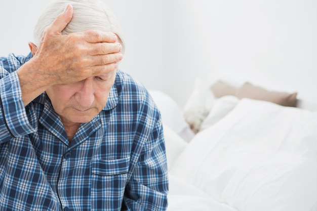 Elderly man suffering on the bed