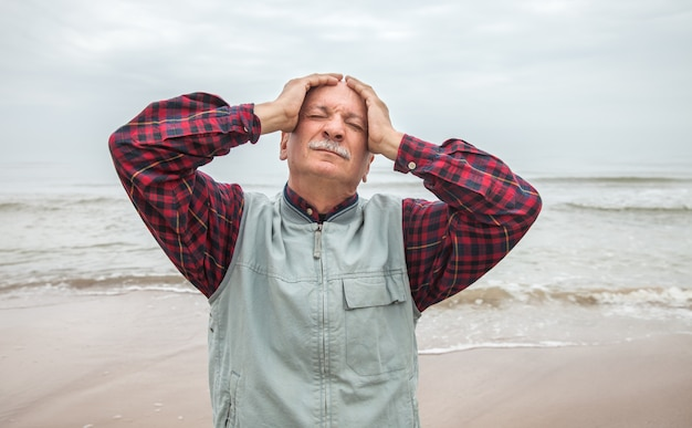 Elderly man suffering from a headache on sea background