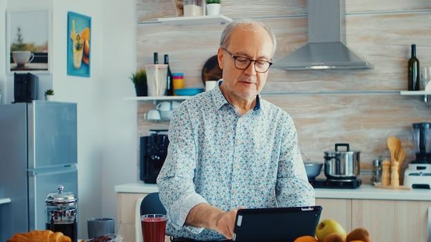 キッチンで朝食時にタブレットコンピューターを使用してインターネットでサーフィンをしている老人。モバイルアプリ、最新のインターネットオンライン情報を使用して定年のタブレットポータブルパッドpcを持つ高齢者