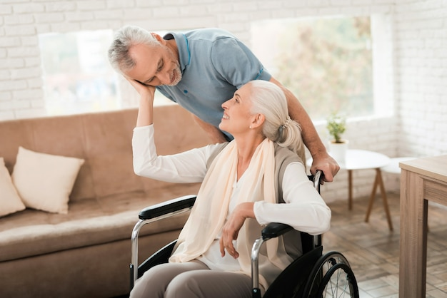 Elderly man take care of mature woman in wheelchair.