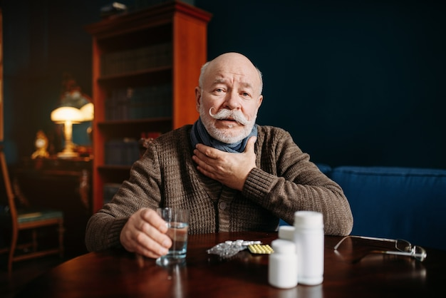 Elderly man takes pills in home office, age-related diseases