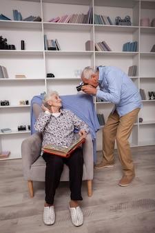 Пожилой мужчина фотографирует женщину