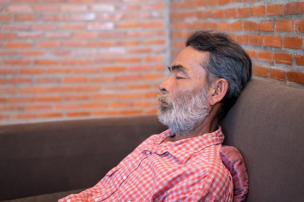 Elderly man taking a nap in sofa at home.