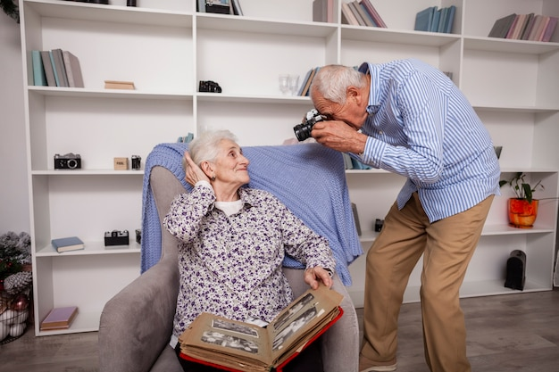 Elderly man taking picture of woman