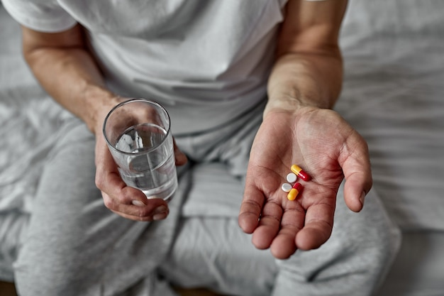Elderly man taking pills, closeup. many pills in hands. caring for the health of the elderly. health issues at an old age, taking several medicines.