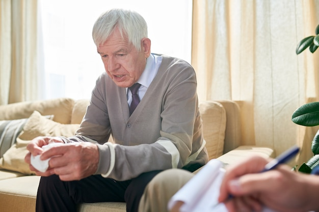 Elderly man talking about his problems at psychotherapy