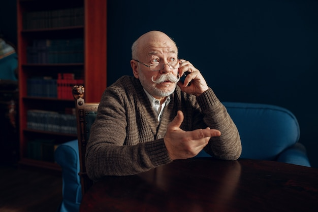 Elderly man talking by mobile phone in home office