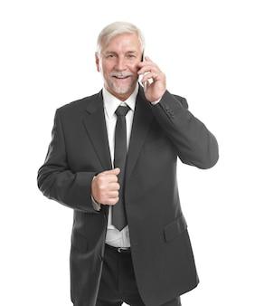 白い背景の上の携帯電話で話している老人