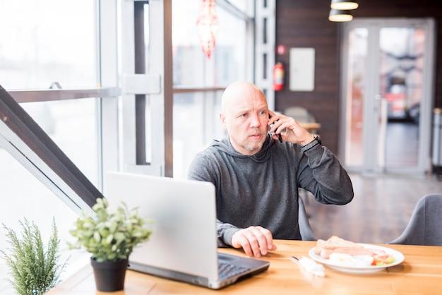 Elderly man talking by mobile phone