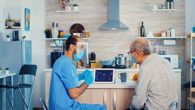 自宅訪問中にコロナウイルスのパンデミックについて医師と話している老人。退職した年配のカップルの男性看護師がcovid-19の広がりを説明し、リスクグループの人々を助けます