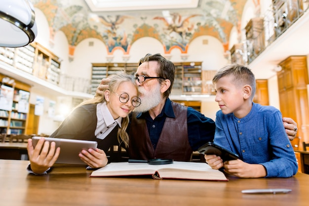 Elderly man teacher and his teen students, boy and girl, sitting at the table in library