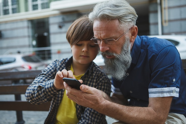 孫とスマートフォンでインターネットを利用している老人