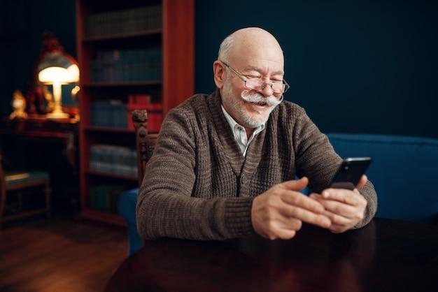 Пожилой мужчина с помощью мобильного телефона в домашнем офисе