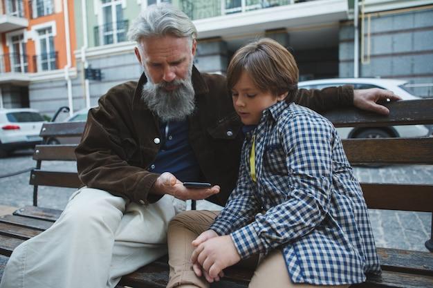 孫の助けを借りてスマートフォンを使用している老人