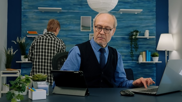 태블릿과 노트북을 동시에 사용하는 노인은 직장에 앉아 집에서 일하는 재무 그래프를 비교하고 있습니다. 보고서 작성, 검색, 분석에 집중하는 바쁜 나이든 직원