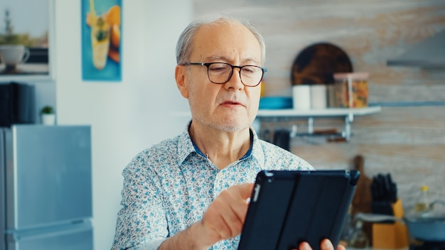 眼鏡をかけて朝食時にキッチンでタブレットpcを使用している老人。モバイルアプリ、最新のインターネットオンライン情報技術を使用して定年のタブレットポータブルパッドpcを持つ高齢者w
