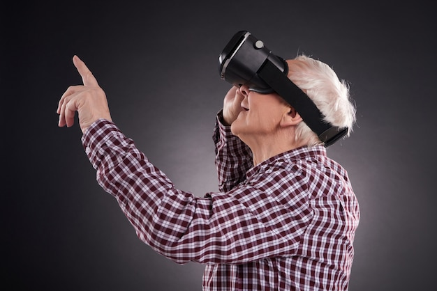 Elderly man in virtual reality glasses on black background.