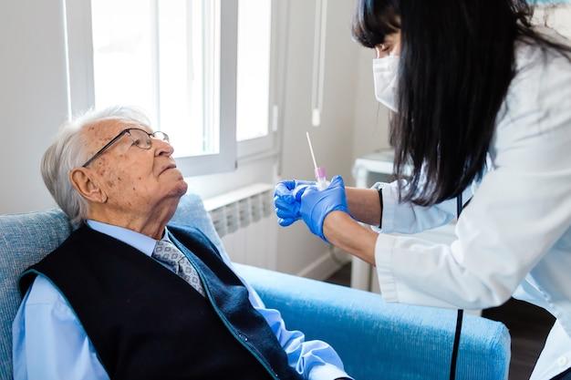노인은 파란색 셔츠와 넥타이를 그의 집에있는 파란색 소파에 앉아 간호사가 그에게 covid 테스트를 줄 것을 기다리고 있습니다. 보건 의료