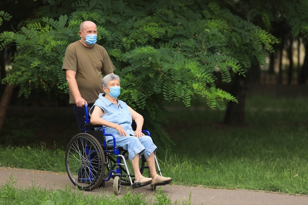 Elderly man walking with disabled elderly woman sitting in wheelchair outdoors wearing medical masks