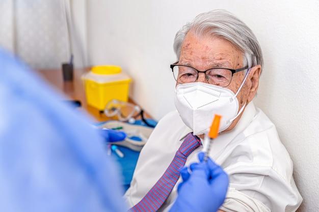 Пожилой мужчина наблюдает, как медсестра в защитном костюме и гигиенических перчатках готовит ему вакцину от коронавируса