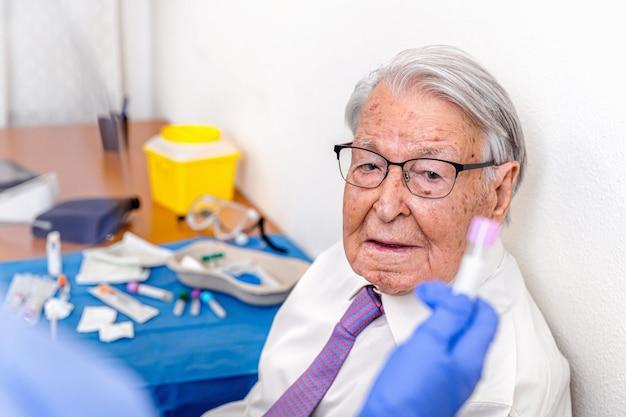 Пожилой мужчина смотрит, как медсестра, одетая в защитный костюм от covid и синие гигиенические перчатки, спасает свой тест на коронавирус.