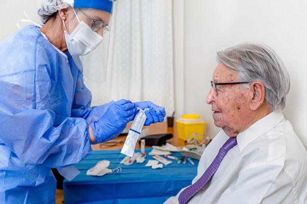코로나 바이러스 보호 복과 마스크를 입고 간호사로 지켜 보는 노인은 검사를 수행하기 전에 코로나 바이러스 검사를 제거합니다.