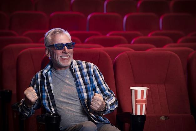 映画館で映画を見ている老人