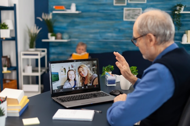 Elderly man waving at camera during online call with his niece