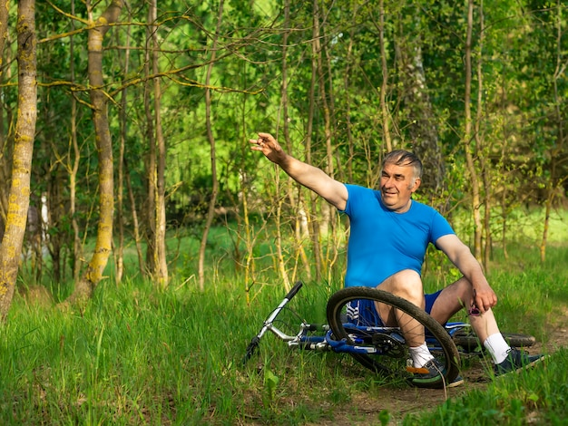 An elderly man waving his hand riding a bicycle