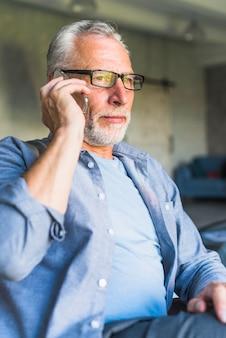 Elderly man wearing black glasses talking on cellphone