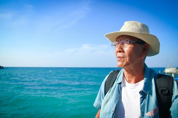 Elderly man wearing a hat happy to travel
