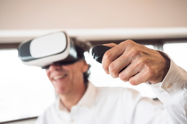 An elderly man wearing virtual reality goggles using remote control