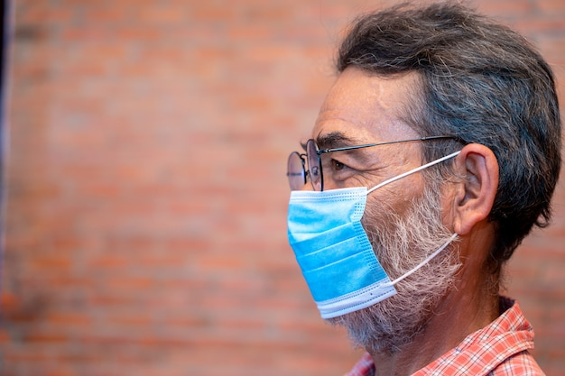 Elderly man wears protective mask against infectious diseases and flu
