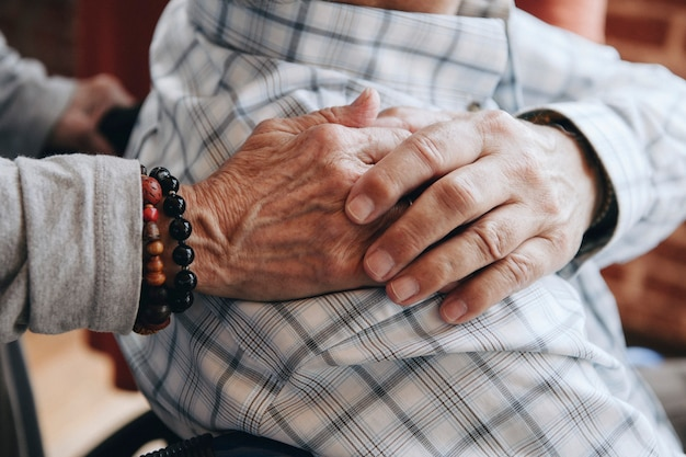 Elderly man on a wheelchair holding his wife hand on his shoulder