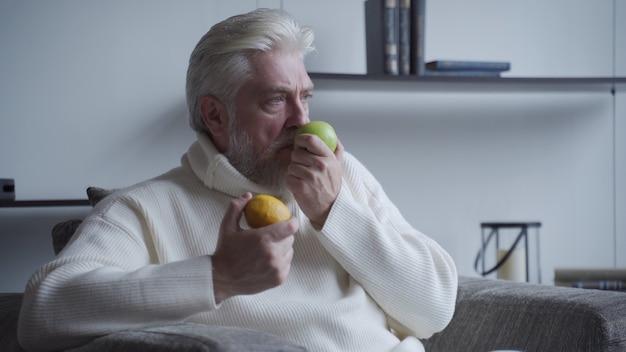 Пожилой мужчина с седой бородой нюхает лимон и яблоко и не пахнет