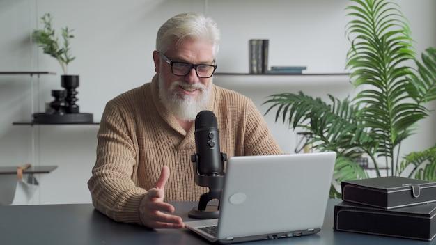 회색 수염을 가진 노인 비디오 블로거가 마이크에 말하기 노인 방송사가 스튜디오에 살고 있습니다.