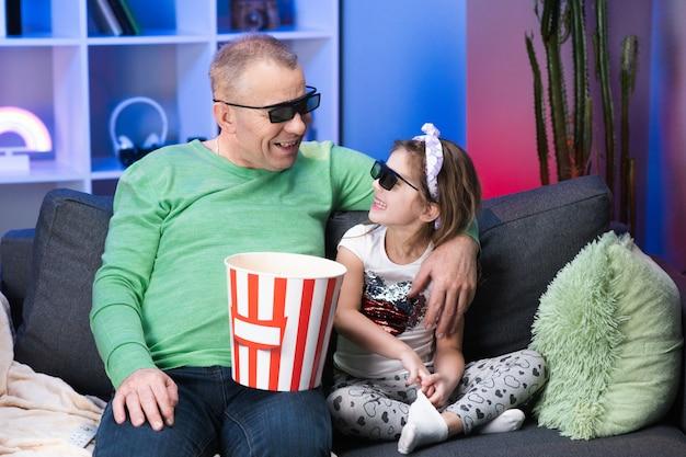 テレビを見ているとポップコーンを食べている3 dメガネを着ている少女と老人。シニア、古い世代、祖父家族の時間は、リビングルームのコンセプトのソファーに若い女の子の子供とリラックスします。