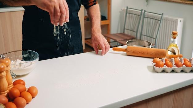 Пожилой мужчина с косточкой и кухонным фартуком просеивает муку на столе, готовую для приготовления пищи. старший пекарь на пенсии с равномерным опрыскиванием, просеиванием, разложением ингредиентов для выпечки домашней пиццы и хлеба.