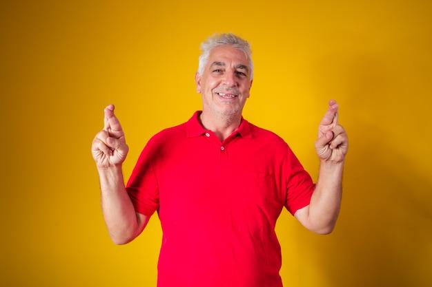 黄色の背景に交差した指を持つ老人。