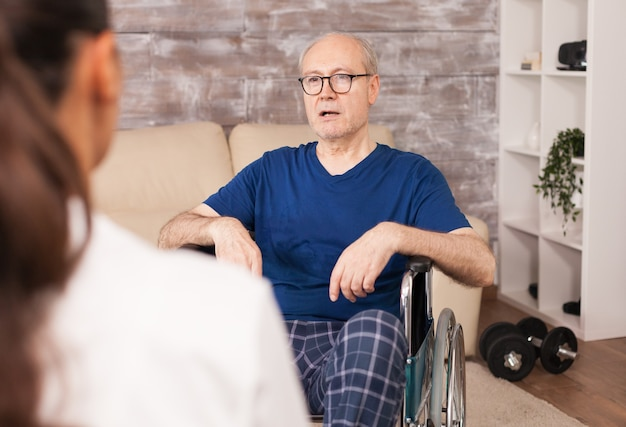 Elderly man with disabilities consulted at home by nurse.