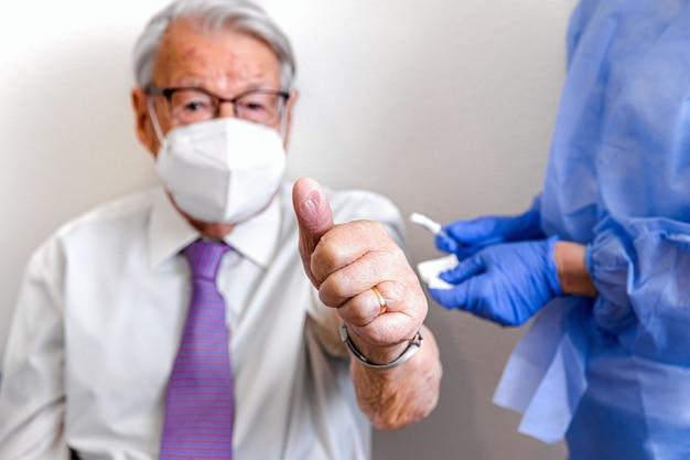 실내에 안경과 마스크를 쓴 노인, 코로나 바이러스 백신 접종 후 만능 상징