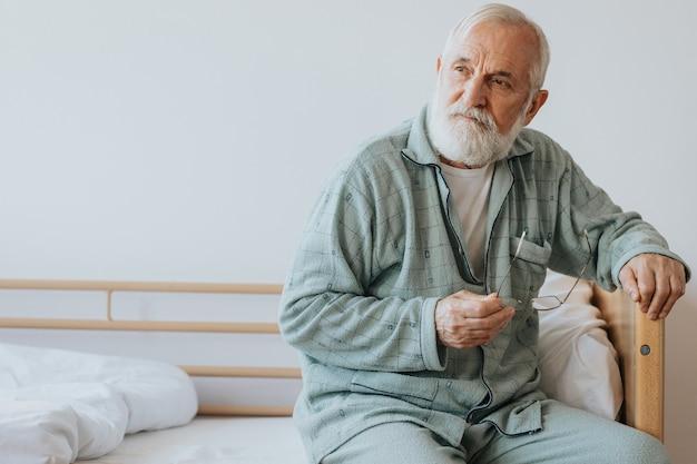 Пожилой мужчина с седой бородой и волосами сидит в пижаме на кровати с очками в руке