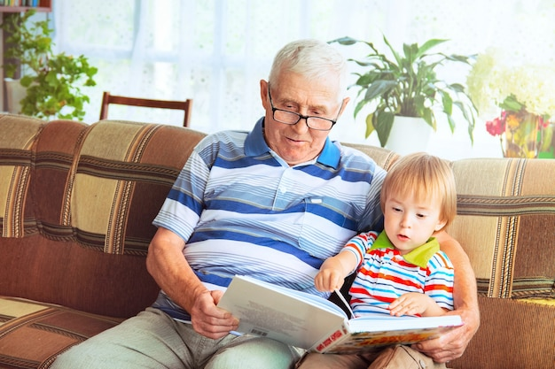 An elderly man with gray hair and glasses is sitting on a sofa with a small boy and holding a book. a grandfather reads a fairy tale to his grandson.