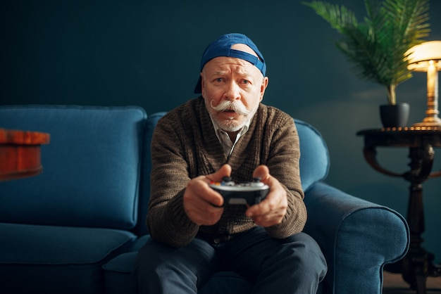 Elderly man with joystick plays a game console on couch